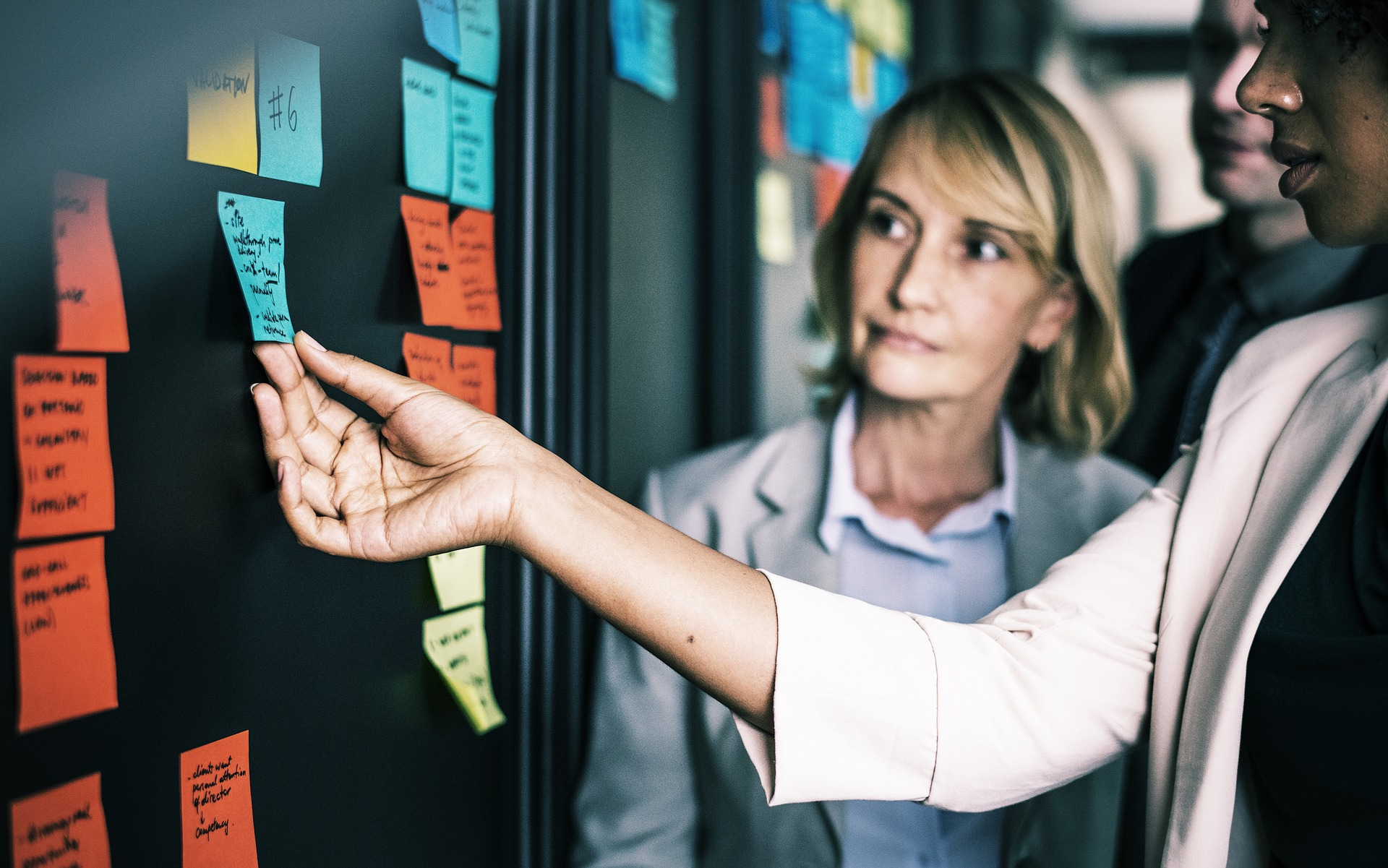 Two Women looking at board with sticky notes